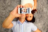 Couple lying on the floor and making selfie photo on smartphone. Focus on smartphone