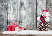 Christmas still life with lantern, snowman, gifts and balls. Wooden planks as background