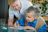stock photo of nurse  - Assisting a senior woman by nurse at home - JPG