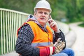 Worker with wrench and a telephone on the bridge