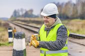 Worker with brush and paint on the railway crossing