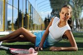 Athletic Healthy Girl Lying On The Grass And Resting After Tennis Outdoors