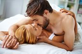 Passionate couple lying on bed and kissing