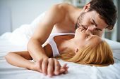 stock photo of sweethearts  - Amorous couple cuddling in bed - JPG