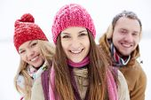 Young friends in winterwear looking at camera with pretty girl in front