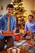 Youthful guy with giftboxes looking at camera with his parents on background