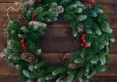 Christmas conifer wreath with firtree cones, red berries and garlands