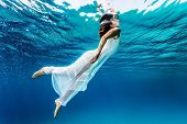 Nice girl emerges from the sea, swimming underwater, enjoying nice refreshing water, wearing long dress, summer vacation and travel concept