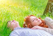 Young lovers resting outdoors, boyfriend and girlfriend lying down on fresh green grass with closed eyes, enjoying romantic relationship, love concept