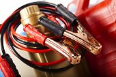 Постер, плакат: Car battery with two jumper cables clipped