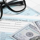 picture of cpa  - US Tax Form 1040 with dollars and glasses