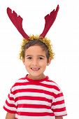 Cute little boy wearing antlers on white background