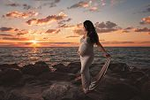 Beautiful Pregnant Woman On The Beach At Sunrise