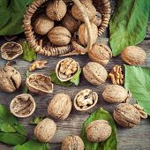 Walnuts And Small Wicker Basket On Old Wooden Table.