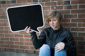 Sad teen girl holds blank sign
