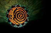 Mosaic lighted ball with sun, moon and spiral design in horizontal position