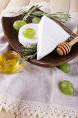 Camembert and brie cheese with grapes on plate and honey in glass bowl on napkin on wooden background