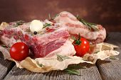 raw bacon with spices and tomatoes on wooden table
