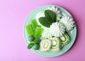 Mint color meringues, mint candies and tasty cake on color background