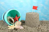 Sandcastle with flag and plastic bucket on sandy beach on sea background
