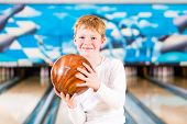 stock photo of bowling ball  - Child bowling with ball in alley - JPG
