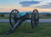 picture of artillery  - This is a piece of Union artillery looking over a farm house at Gettysburg National Military Park at sunset - JPG