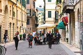 People On A Narrow Street In Verona, Italy