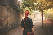 Young Redhead Woman Walking In Alley