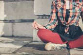 stock photo of soul  - A young woman is sitting and meditating in the street - JPG