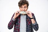 image of choke  - Young casual man biting money over gray background - JPG