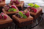 stock photo of racks  - Chocolate mousse brownies with raspberry on a cooling rack - JPG