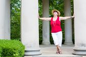 image of grandma  - Happy Feel Good trendy modern grandma leaning with outstretched arms between two columns celebrating the sunshine and nature with her head tilted to the sun - JPG