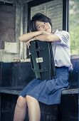 stock photo of daydreaming  - Cute Thai schoolgirl is daydreaming in an old bus stop - JPG