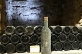 Постер, плакат: Old Bottle Of Wine In The Cellar Of The Winery Ancient Wine Bottles In The Cellar Wineryred Wine Of