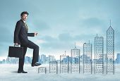 picture of climb up  - Business man climbing up on hand drawn buildings in city concept - JPG