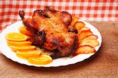 stock photo of roast duck  - Roast duck with apples and oranges on kitchen tablecloth - JPG