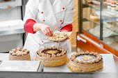 stock photo of biscuits  - Woman making biscuit cake with nuts and chocolate at the bakery - JPG