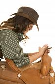 pic of cowgirls  - A cowgirl looking down at the saddle she is leaning on - JPG