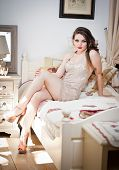 picture of tight dress  - Young beautiful sexy woman in white short tight dress posing challenging indoor on vintage bed - JPG