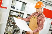 pic of electrical engineering  - adult electrician builder engineer worker with electric scheme plan in front of fuse switch board - JPG