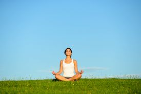 picture of breathing exercise  - Young woman doing yoga relaxing and breathing exercise outdoor - JPG