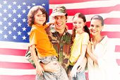stock photo of reunited  - Solider reunited with family against rippled us flag - JPG