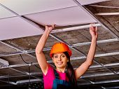 image of millwright  - Woman in builder uniform and orange helmet installing suspended ceiling - JPG