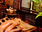 stock photo of panchakarma  - Young woman having Ayurveda stone on back massage - JPG