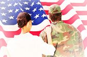 pic of reunited  - Army wife reunited with husband against rippled us flag - JPG