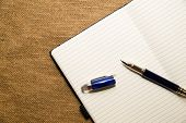 image of memento  - Opened notebook with a blank sheet and pen on the old tissue - JPG
