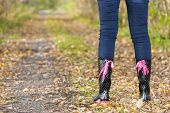 image of woman boots  - detail of standing woman wearing black rubber boots - JPG