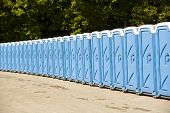 picture of porta-potties  - blue Public toilets in a row on a sunny day - JPG