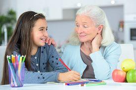 stock photo of grandma  - Little girl drawing wuth grandma - JPG