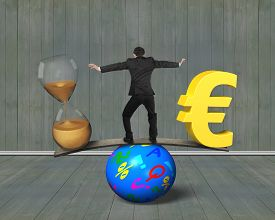 picture of seesaw  - Man standing between hourglass and golden euro sign balancing on seesaw of wood board and colorful ball with wooden wall and floor indoors background - JPG